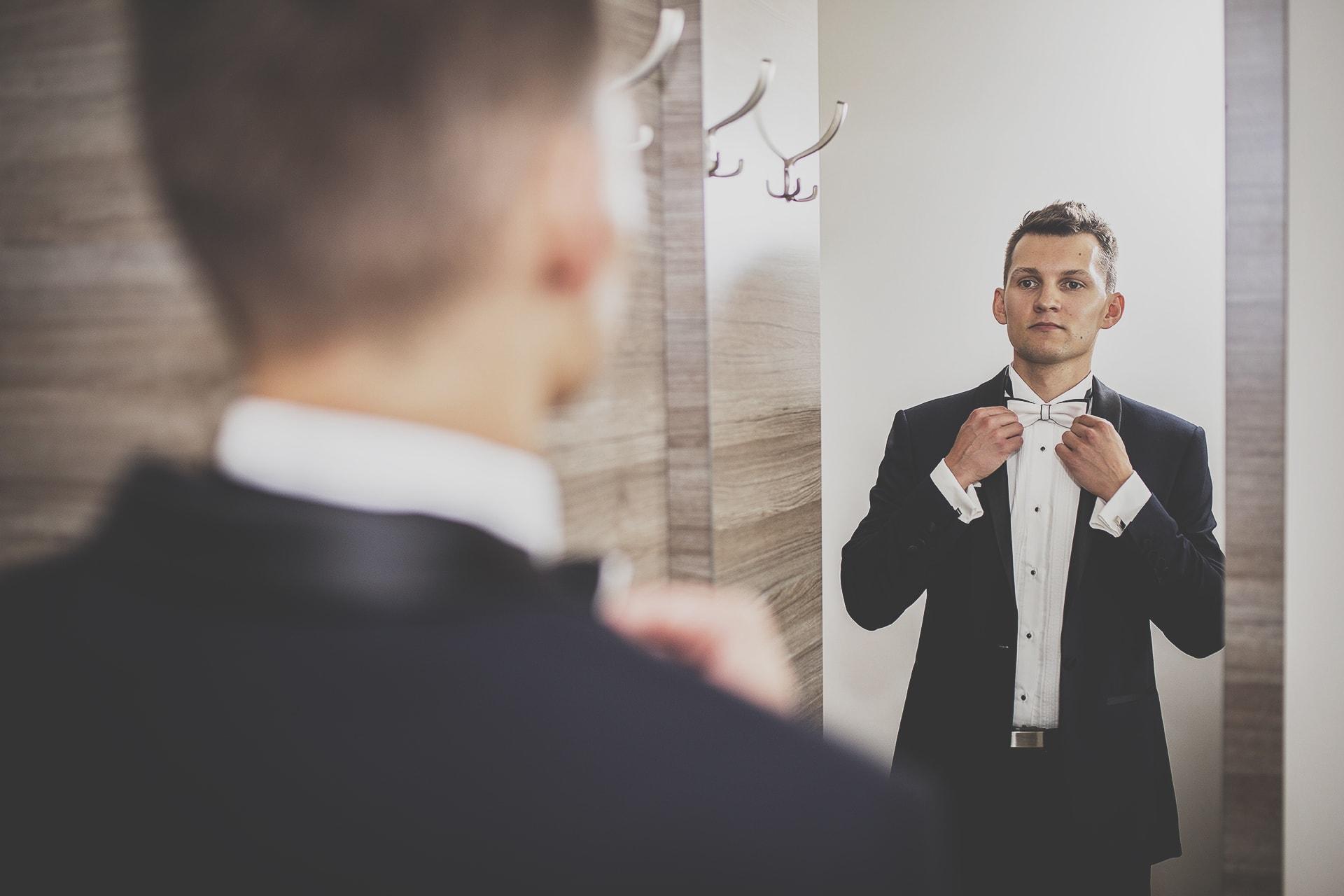 Przygotowania ślubne - pan młody przeglądający się w lustrze